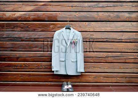 Stylish Elegant Wedding Groom Suit With Buttonhole Hanging On Wooden Background, Copy Space. Gray Su