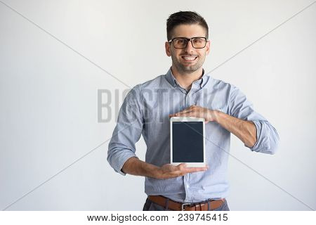 Portrait Of Cheerful Man Wearing Glasses Showing Digital Tablet. Young Caucasian Businessman Wearing