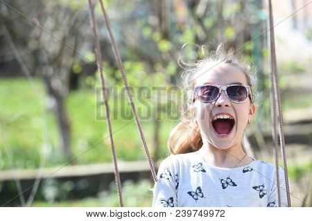 Little Child Smile On Swing In Summer Yard. Fashion Girl In Sunglasses Enjoy Swinging On Sunny Day.
