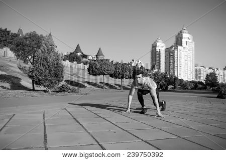 Healthy Lifestyle Concept. Man Runner At Starting Position. Athlete On Asphalt Path On Sunny Summer