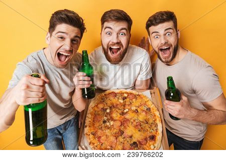 Three young excited men holding a big pizza and drinking beer isolated over yellow background