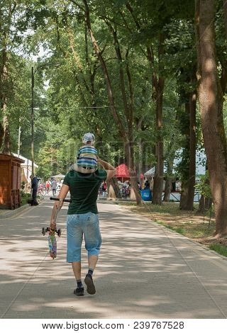 Dad Holds Scooter And His Son On The Neck Walking In A Green Summer Park. Walking A Dad With His Son