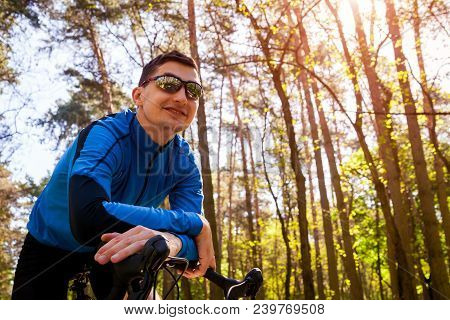 Happy young man bicyclist riding a road bike in spring forest in the morning. Active and healthy way of life concept. Man having rest poster