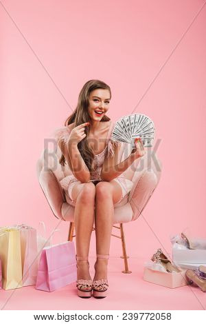 Full length portrait of beautiful shopper woman in dress pointing finger on lots of money in hand while sitting in armchair with purchases isolated over pink background