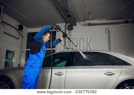 Man Washing Automobile At Manual Car Washing Self Service, Cleaning With Foam, Pressured Water.trans