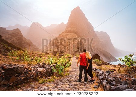 Tourist Couple In Aranhas Valley Hiking From Cruzina To Ponta Do Sol. Huge Mountains Of Coastline An