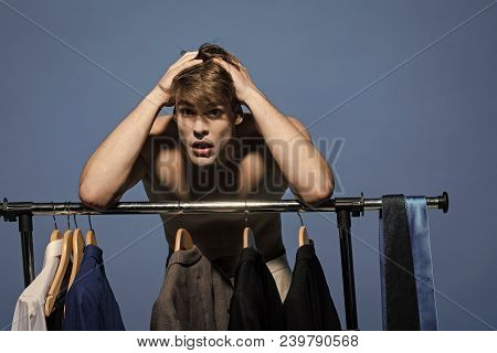 Guy Helpless With Hands On Head Choose Clothes In Wardrobe On Blue Background. Clothing, Dressing, C