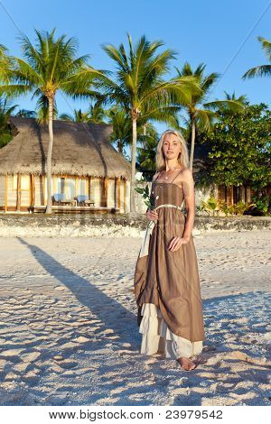 The young woman in a long sundress on a tropical beach. Polynesia. Island Tikehau.