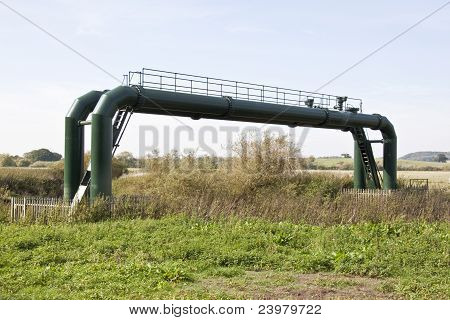 some green water treatment pipes spanning the river poster