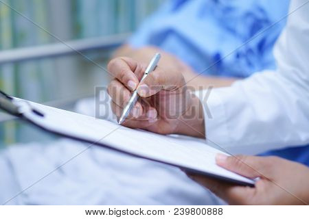 Doctor Writing Down The Diagnosis On Clipboard While Asian Senior Or Elderly Old Lady Woman  Lying O