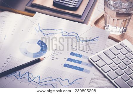 Blue Chart Graph Data Analysis Documents, Pencil, Modern Keybord, Glass Of Water, Calculator, Notebo
