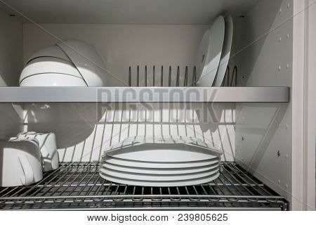 White Porcelain Dishes Dried On Metal Dish Rack. Way To Organize Kitchen And Minimize Space With Mod