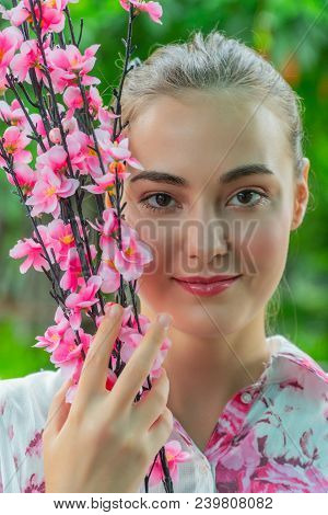 Portrait Charming Beautiful Woman : Attractive Girl Looks So Beautiful. She Holds A Beautiful Pink F