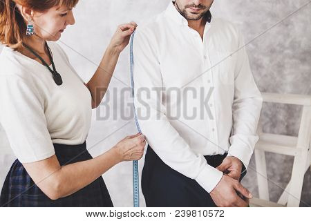 Woman Tailor Takes Measures With Male Models. Fashion Designer Sews A Costume For The Model