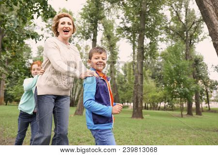 Happy senior woman playing with grandchildren in park
