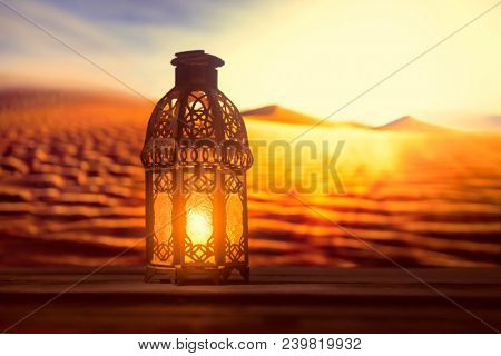 Blessed month of Ramadan. Stock photo. An illuminated Ramadan lamp against a desert background.