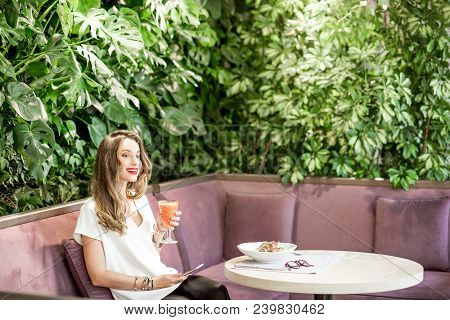 Young And Beautiful Woman Resting At The Beautiful Restaurant With Living Wall Of Green Plants Indoo