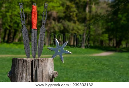 Throwing Knife And Shuriken (throwing Star), On Wooden Background.