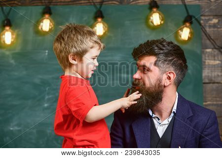 Parenthood concept. Little boy telling something to his dad. Daddy looking at son while kid is playing with his beard. Man and child sideview. poster