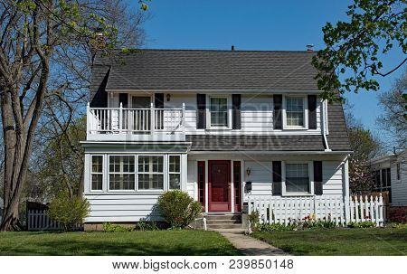 White two-story house with second story balcony or deck over enclosed porch.