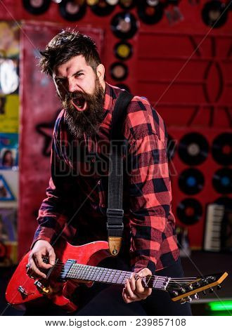 Man With Enthusiastic Face Holds Guitar, Singing Song, Play Music, Music Club Background. Rock Star