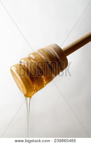 Close Up Of Honey Dripping From Wooden Drizzler.