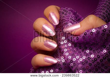 Female Hand With Shiny Purple Nails Is Holding Purple Glittered Textile On Purple Background. Manicu