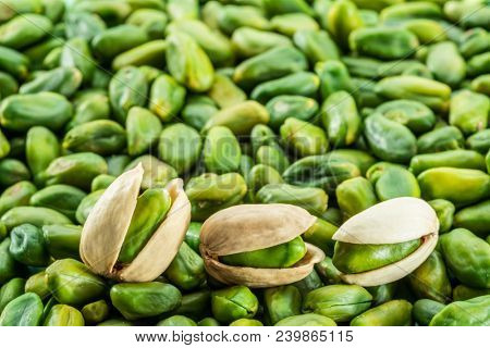 Green pistachio nuts with shell over lot of pistachios . Food background.