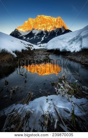 Amazing Scene Of Zugspitze Mountain. Frozen Reflection Of Peak In Cold River. Typical Winter Scene N