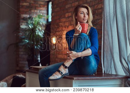 Fashionable Blonde Female Holds Cup Of Coffee While Sitting On A Table Against A Brick Wall In A Stu