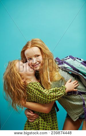Little Girl Kissing Her Older Sister On Blue Background. Warm And Friendly Relations Between Relativ