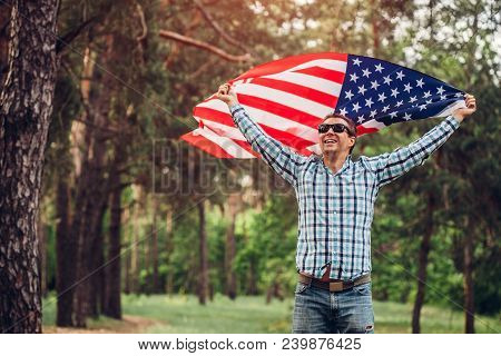 Happy Man Running With Usa Flag In Park At Sunset. Celebrating Independence Day Of America. July 4th