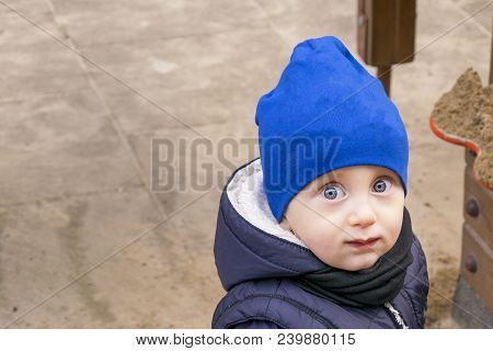 Waist Up Portrait Of Happy Boy In Stylish Cap And Jacket. Kid With Amazing Blue Eyes Standing And Lo