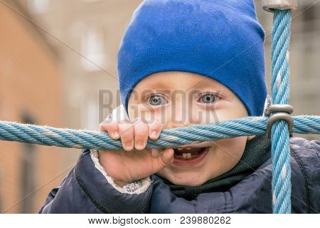 Waist Up Portrait Of Interested Kid Having Fun Time On Playground. Laughing Child With Amazing Blue