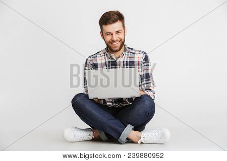 Portrait of a handsome young man in plaid shirt sitting on a floor with laptop computer isolated over white background