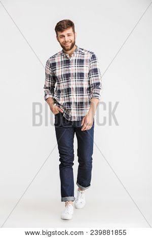 Full length portrait of a confident young man in plaid shirt walking and looking at camera isolated over white background