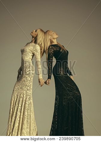 Two Girls With Long Blond Hair Posing On Grey Sky. Opposites And Contrasts Concept. Choice, Decision