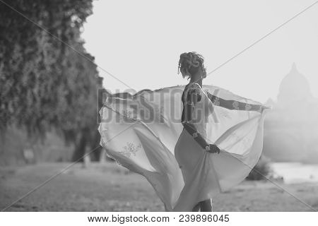 Back View Of Pretty Lovely Blond Bride In Long White Wedding Dress With Train Spinning Outdoor Sunny