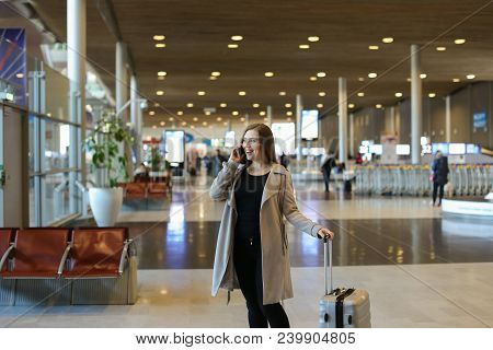 Nice Young Woman Going In Airport Waiting Room With Valise And Speaking By Smartphone. Concept Of Tr