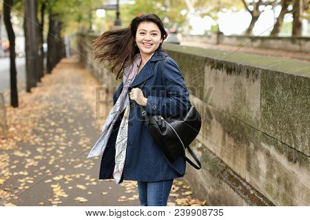 Asian Young Female Tourist Walking On Autumn Street With Fallen Leaves In Europe. Concept Of Interna