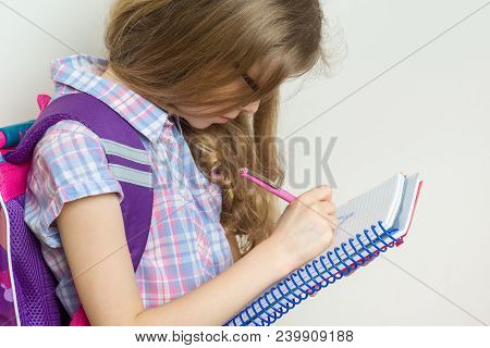 Girl Child Elementary School Student Wearing Glasses With A Backpack Writing In Her Notebook. Bright