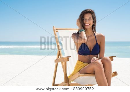Happy smiling woman sitting on deck chair at sea. Young woman sunbathing in blue bikini while sitting with copy space. Laughing girl enjoying the sun at beach while looking at camera.