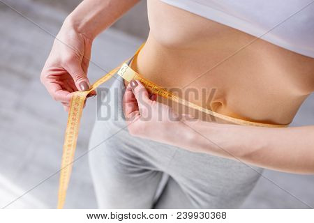 Waist Size. Nice Slim Woman Holding A Centimeter Tape While Measuring Her Waist