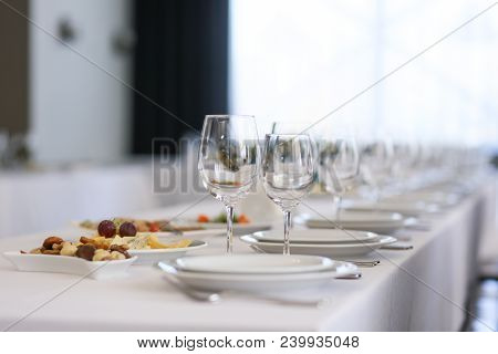 A Row Of Crystal Glasses And White Plates On A Festive Table In A Restaurant
