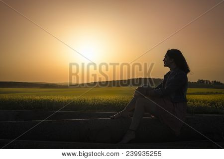 Silhouette Of A Woman Gazing The Horizon, Admiring The Sunset Over Rapeseed Fields, In South Moravia