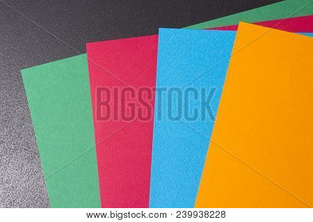 Multi-colored Sheets Of Paper On A Black Background. Sheets Of Paper Of Different Colors. Colored Sh