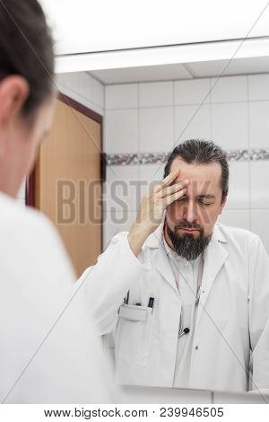 Doctor In Front Of A Mirror Have Headache And Looks Stressed Near To An Burnout