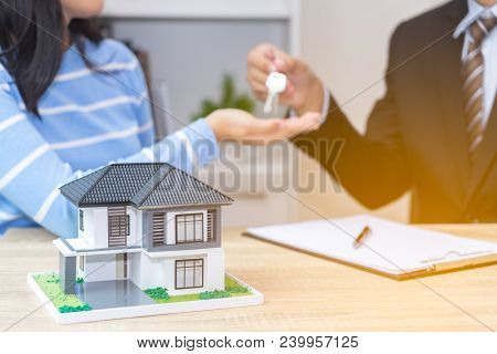Businessman Or Sale Man Giving A House Key To Woman -  Buying Home Concept With Fair.