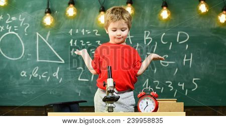 Kid Boy Near Microscope, Clock In Classroom, Chalkboard On Background. First Former Confused With St