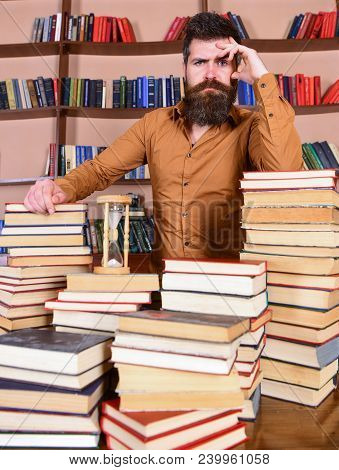 Librarian Concept. Man On Thoughtful Face Stands Between Piles Of Books, While Studying In Library,
